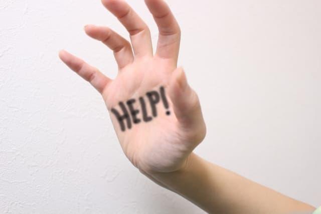 「Help」と描いた手の画像